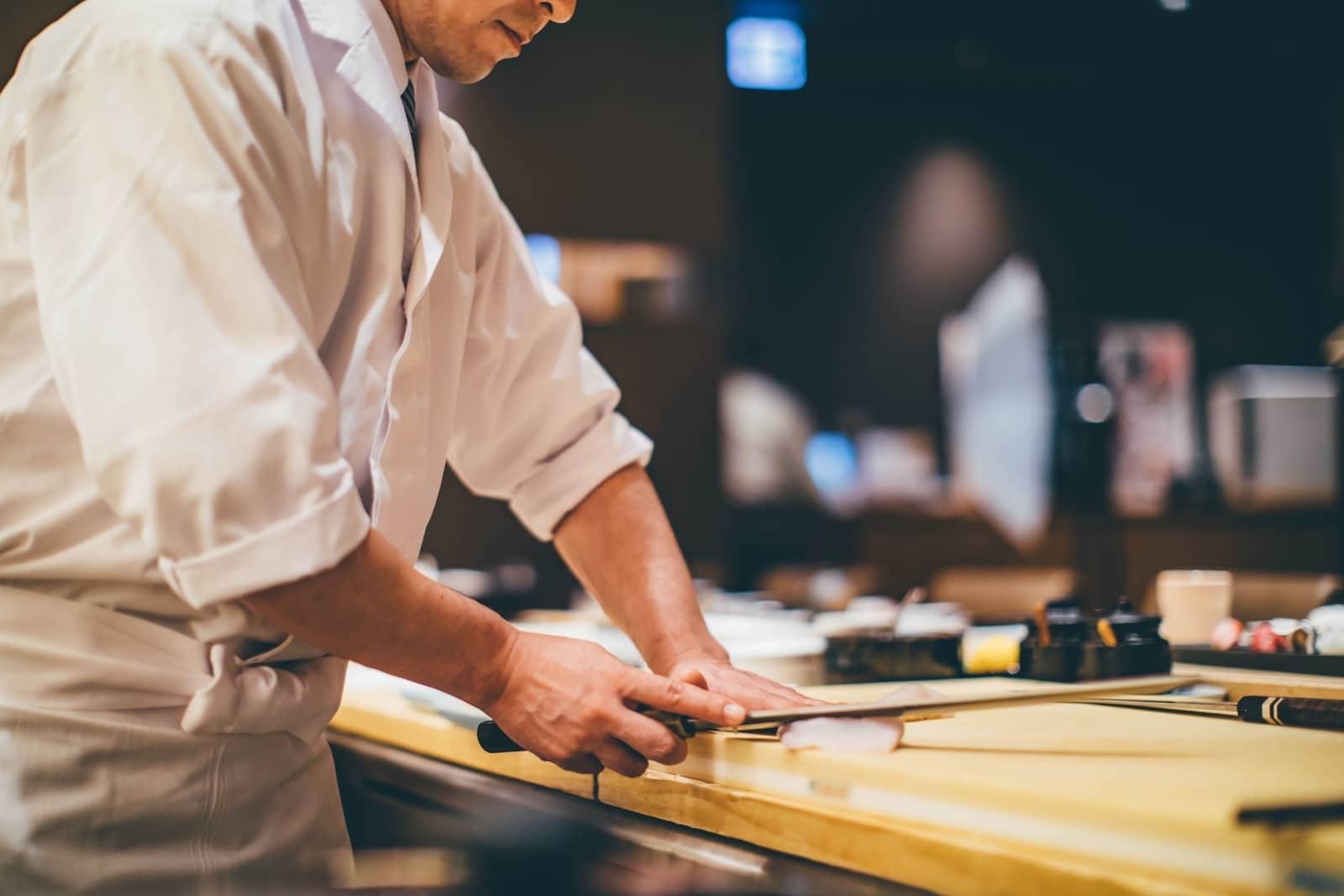 Sushi chef cutting fish