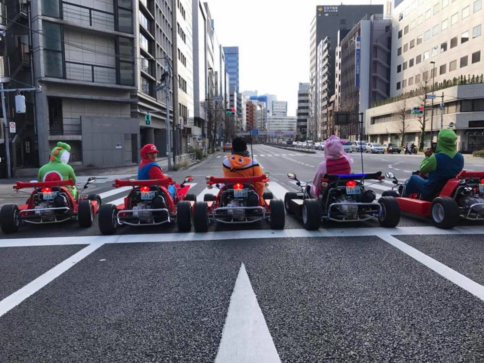 People driving a go-kart wearing characters' costumes