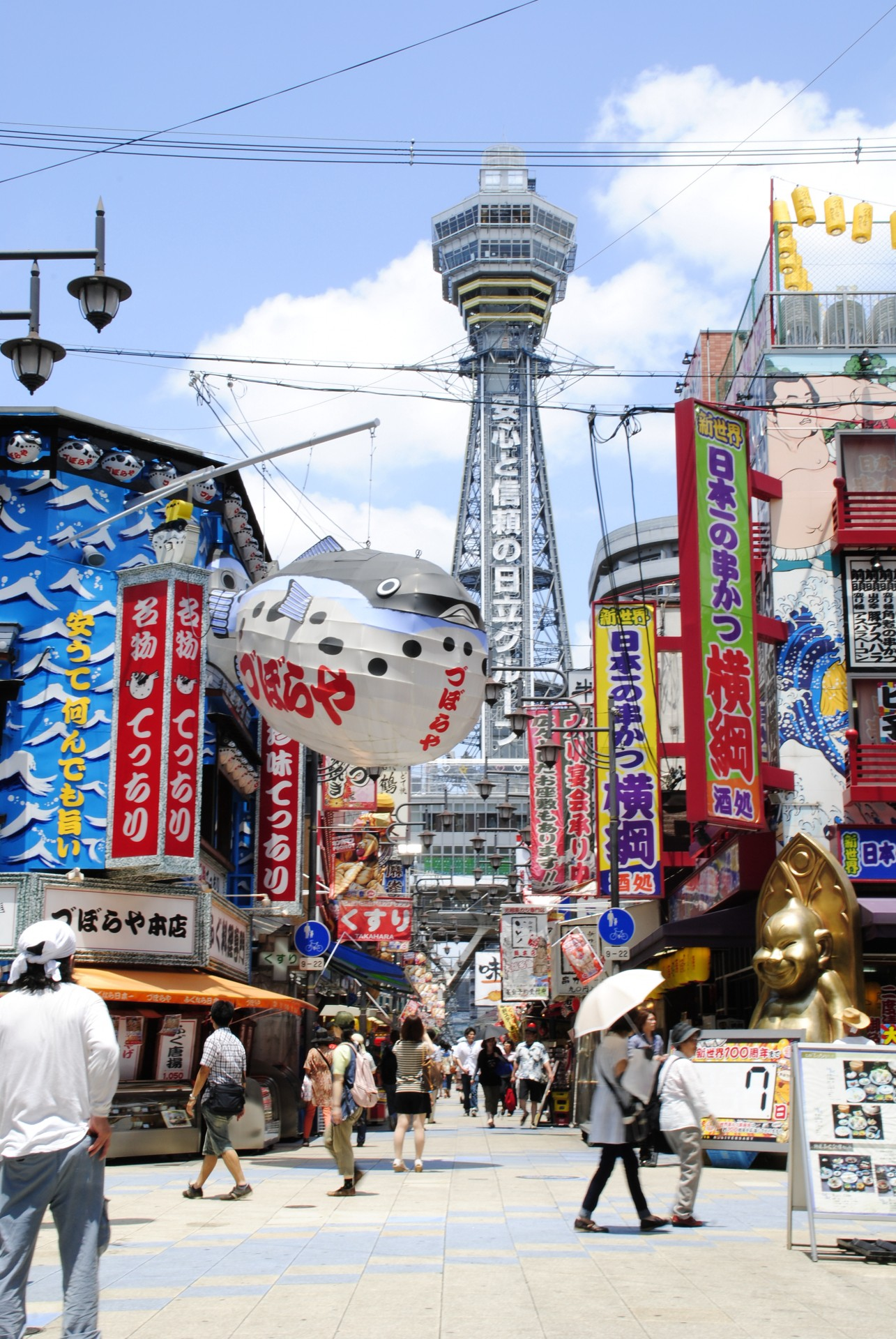 The street of Shinsekai district with colourful shop signs and Tsutenkaku Tower