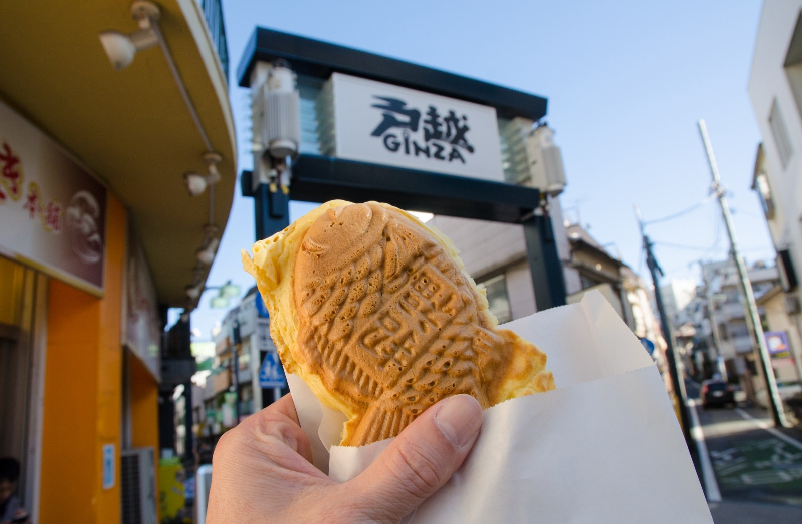 A portable snack and the entrance of Togoshi Ginza Shopping Street