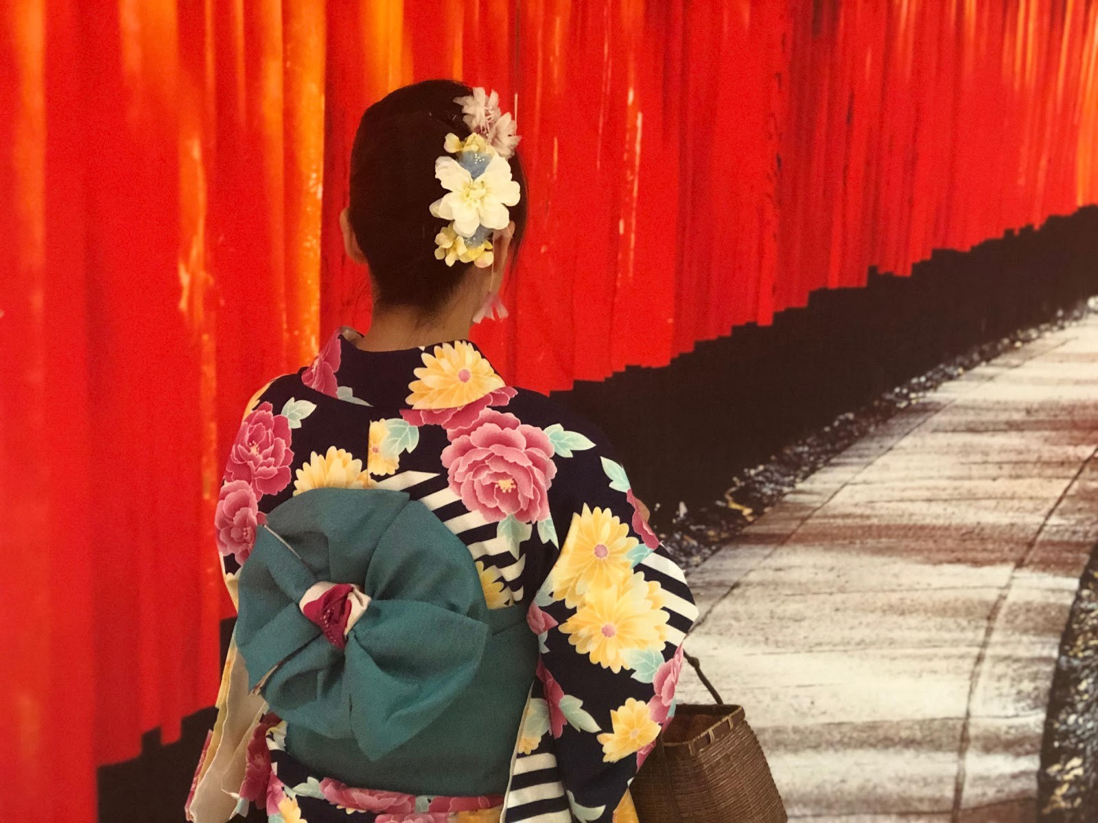 A girl is walking at Fushimi Inari wearing Kimono