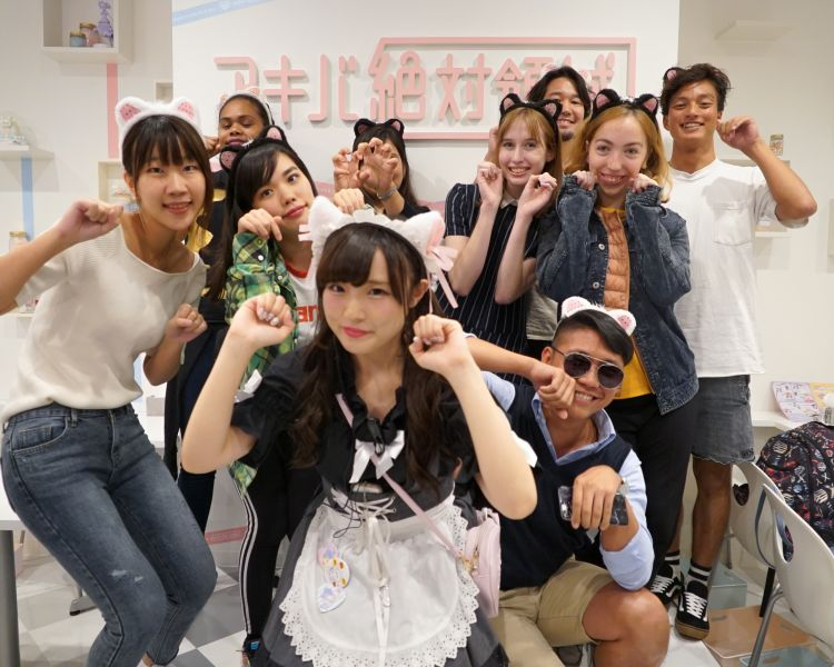 A maid and guests at Maid Cafe